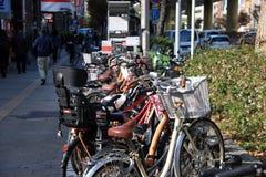 Muchos montan en bicicleta el parque en el estacionamiento de la bicicleta en la acera al lado del camino en Namba, Japón imagen de archivo