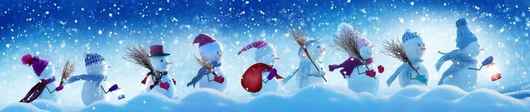 Muchos muñecos de nieve que se colocan en paisaje de la Navidad del invierno fotos de archivo
