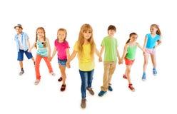Muchos muchachos y muchachas se colocan juntas que llevan a cabo las manos Imágenes de archivo libres de regalías