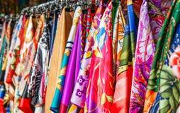 Muchos neckerchiefs de seda brillantes en el estante de la tienda imágenes de archivo libres de regalías
