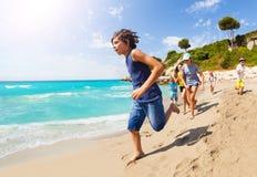Muchos niños corren en la diversión de la playa arenosa y el tener Imagen de archivo libre de regalías