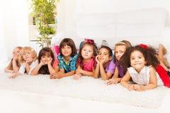Muchos niños en fila en el piso en casa Fotos de archivo