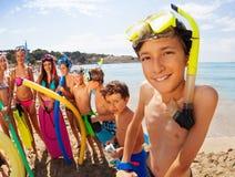 Muchos niños en la playa con el muchacho en máscara que bucea Imagen de archivo