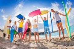 Muchos niños en una playa con las herramientas y los juguetes de la natación Imagenes de archivo