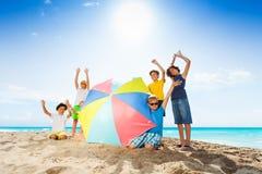 Muchos niños que se colocan con el paraguas de sol en la playa Fotografía de archivo libre de regalías