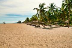 Muchos ociosos vacíos del sol en la playa abandonada de la isla de Hainan foto de archivo libre de regalías