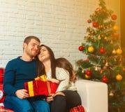Muchos ornamentos y regalos del día de fiesta Familia joven feliz con los presentes por Año Nuevo Fotografía de archivo libre de regalías