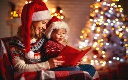 Muchos ornamentos y regalos del día de fiesta libro mágico de la lectura de la madre y del bebé de la familia en casa fotografía de archivo libre de regalías