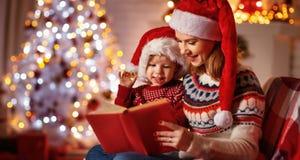 Muchos ornamentos y regalos del día de fiesta libro mágico de la lectura de la madre y del bebé de la familia en casa fotografía de archivo
