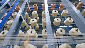 Muchos ovillos que giran mientras que arrolla los hilos en una instalación moderna de materia textil metrajes