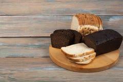 Muchos panes y rollos mezclados del pan cocido en fondo de madera de la tabla fotos de archivo libres de regalías