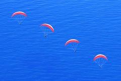 Muchos paracaídas del rojo en el cielo sobre el mar azul Imagen en el estilo del minimalismo Imagenes de archivo