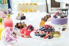 Muchos pasteles dulces en la tabla blanca con las bayas frescas del verano FE imágenes de archivo libres de regalías
