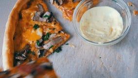 Muchos pedazos de pizza con diversos rellenos, aceitunas, pollo, setas, queso, tocino, salami, verdes al lado de la salsa almacen de metraje de vídeo