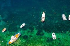 Muchos pequeños barcos de pesca en la onda del agua de la turquesa, Scilla, AIE imagen de archivo