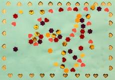 Muchos pequeños corazones y flores de papel en fondo verde Fotos de archivo