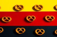 Muchos pequeños pretzeles en un fondo de los colores alemanes de la bandera Fotos de archivo libres de regalías