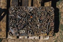 Muchos pernos oxidados, nueces, lavadoras, clavos, recambios en una caja del metal foto de archivo