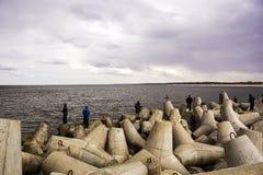 Muchos pescadores cogen pescados en el mar que se coloca en los cantos rodados grandes Fotografía de archivo libre de regalías