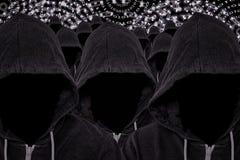 Muchos piratas informáticos de ordenador anónimos encapuchados con código binario imagen de archivo