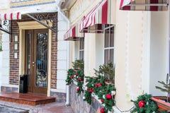 Muchos que brillan, bolas brillantes del árbol de navidad, decoración en las ventanas de un restaurante, café Pared de ladrillo,  Fotografía de archivo