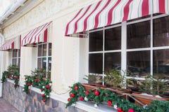 Muchos que brillan, bolas brillantes del árbol de navidad, decoración en ventanas de un restaurante Imagen de archivo