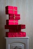 Muchos regalos rojos en el nightstand Foto de archivo libre de regalías