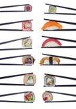 Muchos rollos de sushi en los palillos aislados en blanco Fotos de archivo libres de regalías