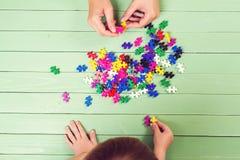 Muchos rompecabezas en la tabla de madera El niño conecta rompecabezas Fotografía de archivo