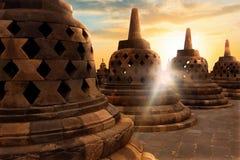 Muchos stupas budistas de piedra enormes contra la perspectiva de la salida del sol con los rayos de la luz en el templo de Borob foto de archivo