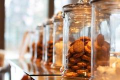 Muchos tarros de cristal con los casquillos llenados de las galletas y de los dulces, en fondo defocused con la reflexión Los tar fotos de archivo libres de regalías