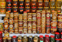 Muchos tarros del vidrio con el atasco, la miel y las nueces Imagen de archivo libre de regalías