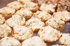 Muchos tartlets con la ensalada rusa en la tabla de comida fría Fotografía de archivo libre de regalías