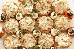 Muchos tartlets con la ensalada rusa en la tabla de comida fría Foto de archivo libre de regalías
