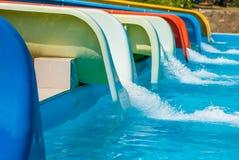 Muchos toboganes acuáticos coloridos en parque del agua de la diversión y piscina azul del verano Imágenes de archivo libres de regalías