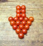 Muchos tomates rojos maduros como flecha firman en superficie de madera Fotos de archivo