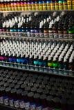 Muchos tubos de la pintura del tatuaje en el escaparate Imagen de archivo libre de regalías