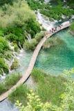 Muchos turistas caminan las trayectorias en el parque nacional de los lagos Plitvice Imagen de archivo libre de regalías