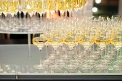 Muchos vidrios con champán o el vino blanco en el abastecimiento del evento Fotos de archivo