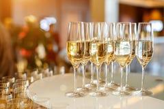 Muchos vidrios con champán o el vino blanco en el abastecimiento del evento Imagen de archivo