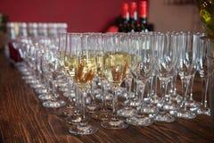 Muchos vidrios con el vino blanco en la tabla de comida fría Foco suave, foco selectivo Foto de archivo