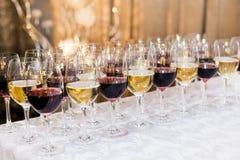 Muchos vidrios con el vino blanco y rojo en la tabla de comida fría Foto de archivo