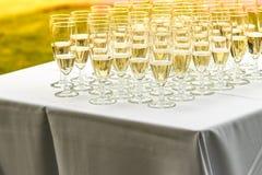 Muchos vidrios de champán en la tabla blanca Imágenes de archivo libres de regalías