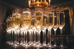 Muchos vidrios de champán en una atmósfera lujosa Foto elegante, entonada Foto de archivo libre de regalías