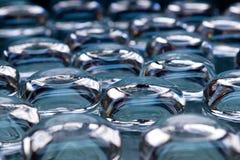 Muchos vidrios transparentes en fondo azul Fotos de archivo libres de regalías
