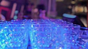 Muchos vidrios vacíos de cristal están uno al lado del otro en sitio oscuro en el contador de la barra almacen de video