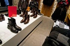 Muchos zapatos y ropa en estantes de una tienda del departamento Imágenes de archivo libres de regalías