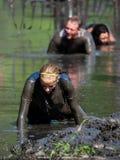 Mucking through the mud. Athletes crawl through the thick mud, during the July 2014 mudathlon in northwest Indiana Royalty Free Stock Photo