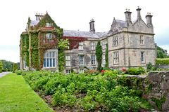 Muckross House and rose garden, Killarney, Ireland. Muckross House, County Kerry, Ireland - is a Tudor style mansion built in 1843 located on the small Muckross Stock Photography