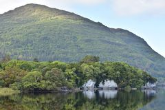 Muckross Lake reflections. Reflections of hills forests and rock formations on calm surface of Muckross Lake in Ireland stock photos